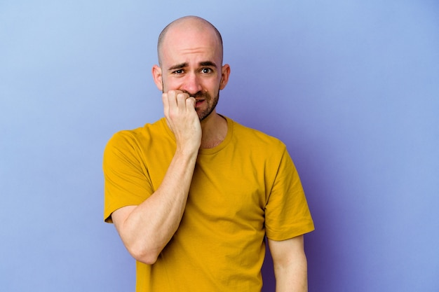 Young caucasian bald man isolated on purple wall biting fingernails, nervous and very anxious.