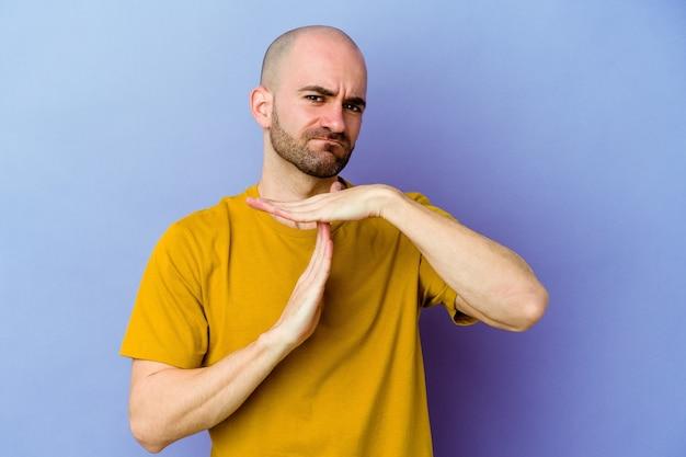 Молодой кавказский лысый мужчина на фиолетовом, показывая жест тайм-аута.