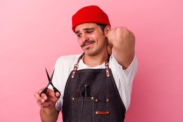 Молодой кавказский парикмахер держит ножницы, изолированные на розовом фоне, касаясь затылка, думая и делая выбор.