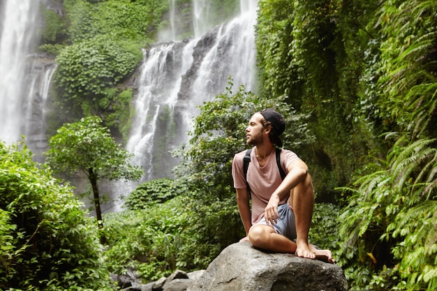 Young caucasian barefooted male tourist with backpack sitting on rock surrounded by rainforest and admiring gorgeous view with waterfall