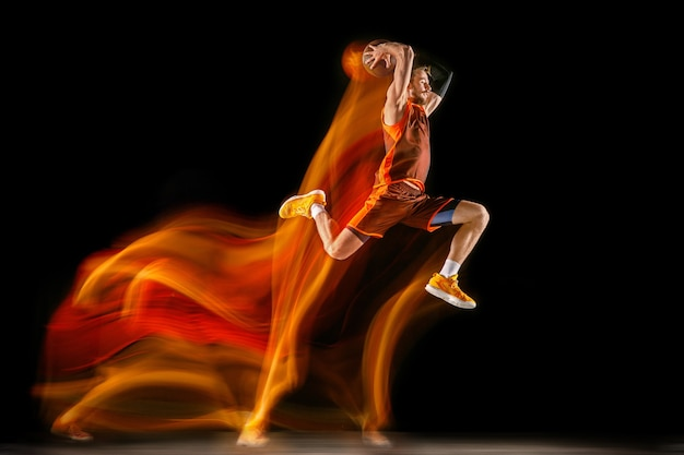 Молодой кавказский баскетболист на темном фоне в смешанном свете