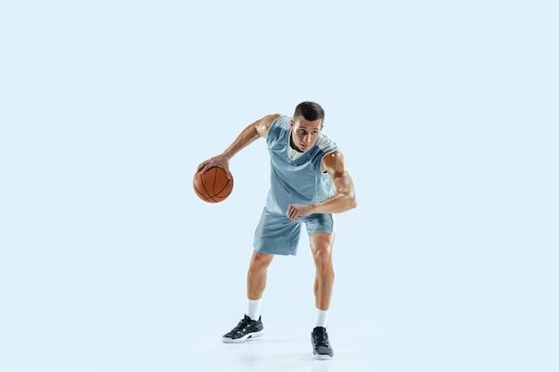 白いスタジオに対する若い白人バスケットボール選手