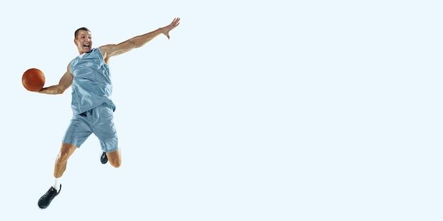 활동 중인 백인 젊은 농구 선수, 파란색 배경에 격리된 점프 동작. 스포츠, 운동, 에너지 및 역동적이고 건강한 생활 방식의 개념. 훈련. 광고 전단지.