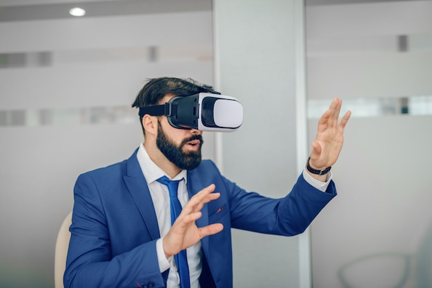 Young caucasian bearded businessman in blue suit using vr goggles at office.