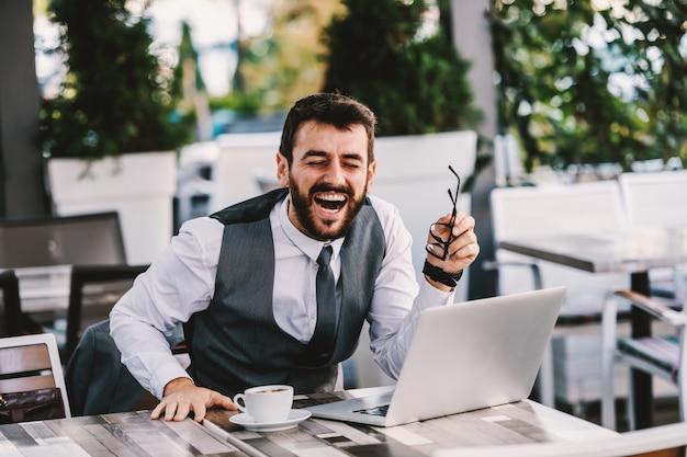 カフェに座っていると彼がインターネットで読んだ冗談について笑っているスーツの若い白人のひげを生やした実業家。コーヒーブレイク。