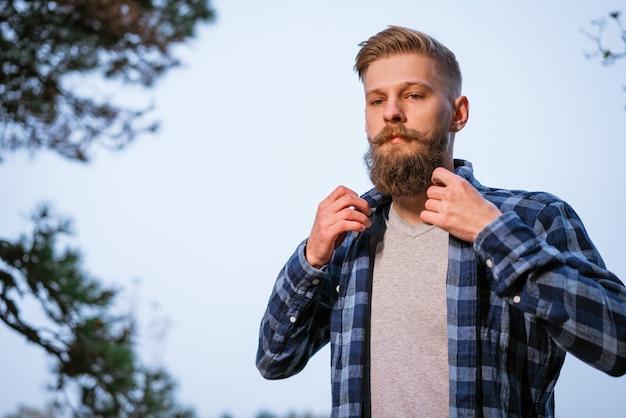 秋の森を一人旅し、横を向いている格子縞のシャツを着た若い白人のひげを生やした男