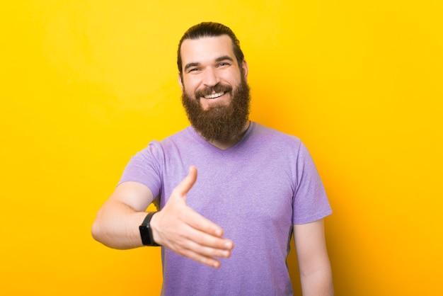 Молодой кавказский бородатый мужчина протягивает руку для рукопожатия.