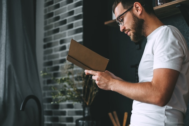 台所で本を読んでいる若い白人のひげを生やした男。ホームレジャー。
