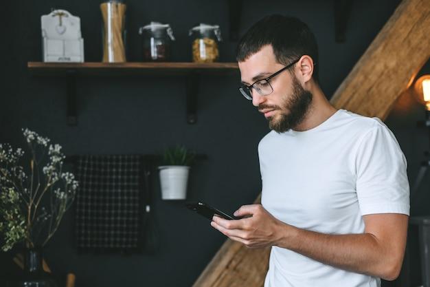キッチンでスマートフォンを使用して若い白人のひげを生やした男。