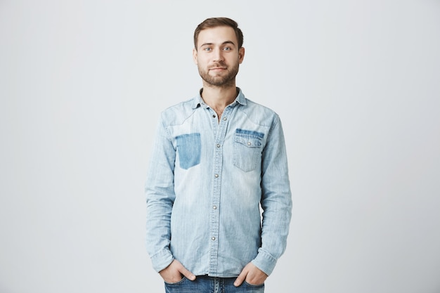 Young caucasian bearded man with hands in pockets