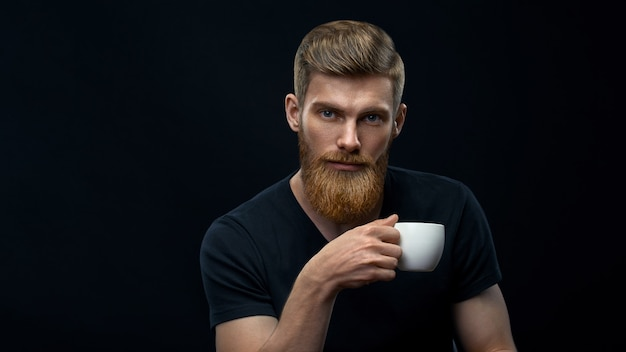Young caucasian bearded stylish man with cup of coffee. handsome hairstyling male portrait holding coffee cup over black background.
