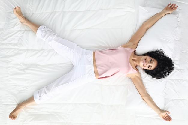 Молодая кавказская beaty женщина лежит на белом портрете взгляд сверху кровати.