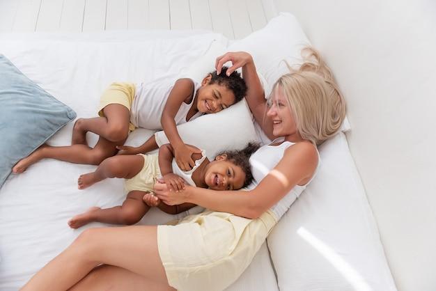 若い白人の金髪の母親が遊ぶ、アフリカ系アメリカ人の娘の息子と白いベッドに横たわる
