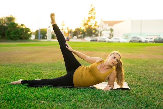 Giovane femmina bionda caucasica che pratica yoga nel parco