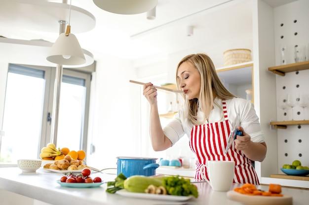 Молодая кавказская блондинка в красном полосатом фартуке пробует суп деревянной ложкой на кухне