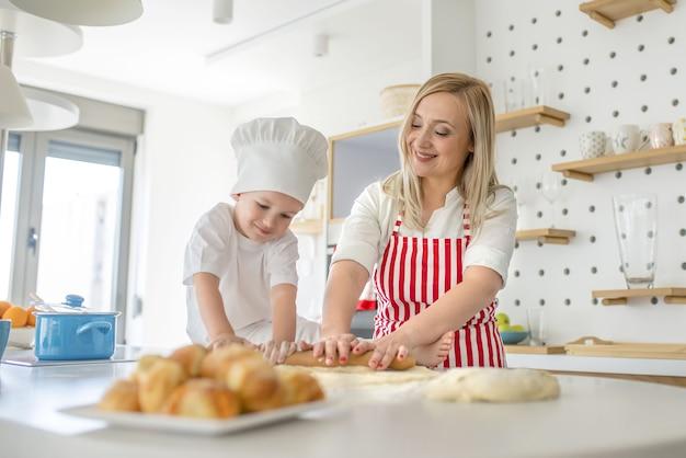 Молодая кавказская белокурая женщина в полосатом фартуке помогает своему сыну в шляпе шеф-повара, сидящему на th