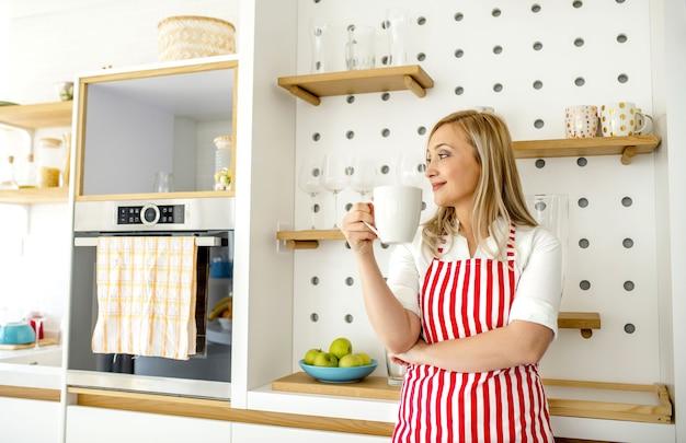 Молодая кавказская блондинка в красном полосатом фартуке держит кружку, глядя в сторону, улыбаясь на кухне