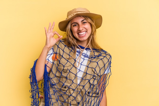 黄色の背景に分離されたロッドを保持している若い白人の金髪の漁師は、陽気で自信を持って大丈夫なジェスチャーを示しています。