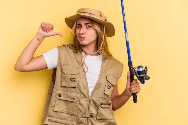 Молодая кавказская блондинка-рыбак, держащая удочку, изолированную на желтом фоне, чувствует себя гордой и уверенной в себе, примером для подражания.