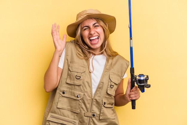 Молодая кавказская блондинка-рыбак держит штангу, изолированную на желтом фоне, получая приятный сюрприз, возбужденный и поднимающий руки.