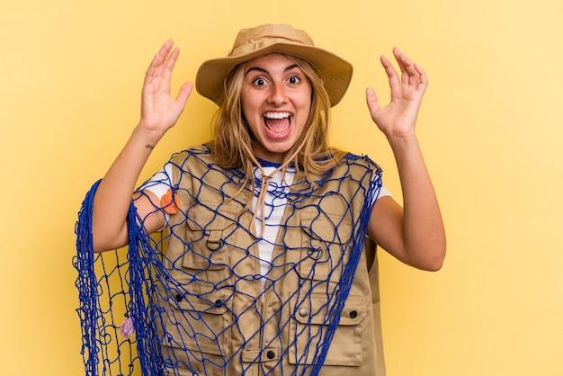 黄色の背景に分離されたロッドを保持している若い白人の金髪の漁師は、嬉しい驚きを受け取り、興奮し、手を上げます。