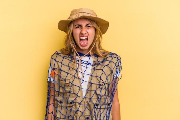 非常に怒って攻撃的な叫び声黄色の背景に分離されたロッドを保持している若い白人の金髪の漁師。