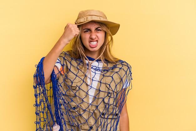 カメラに拳、攻撃的な表情を示す黄色の背景に分離されたロッドを保持している若い白人金髪漁師。