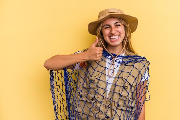 Молодая кавказская блондинка-рыбак держит удочку, изолированную на желтом фоне, улыбается и поднимает большой палец вверх