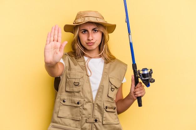 Молодая кавказская белокурая рыбачка держит штангу, изолированную на желтом фоне, стоя с протянутой рукой, показывая знак остановки, предотвращая вас.