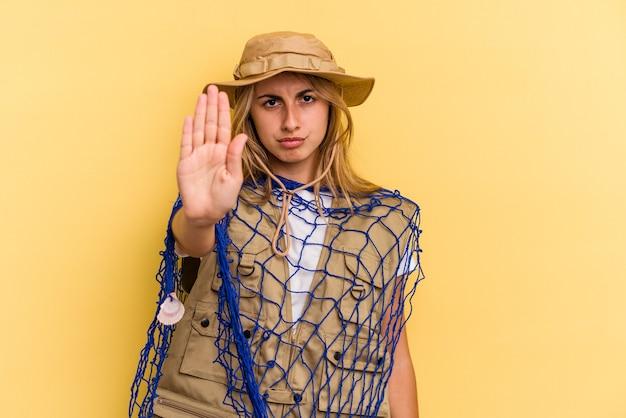 黄色の背景に分離されたロッドを保持している若い白人の金髪の漁師は、一時停止の標識を示している手を伸ばして立って、あなたを防ぎます。