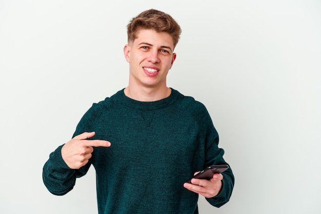 Young caucasian blonde man using a telephone isolated on white wall person pointing by hand to a shirt copy space, proud and confident