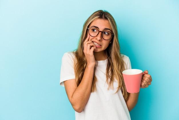 青い背景で隔離のマグカップを保持している若い白人のブロンドの女性は、コピースペースを見ている何かについて考えてリラックスしました。
