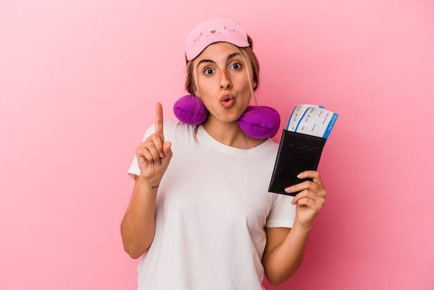 여권과 티켓을 들고 젊은 백인 금발의여자가 몇 가지 좋은 아이디어, 창의성의 개념을 갖는 분홍색 배경에 고립 된 여행.