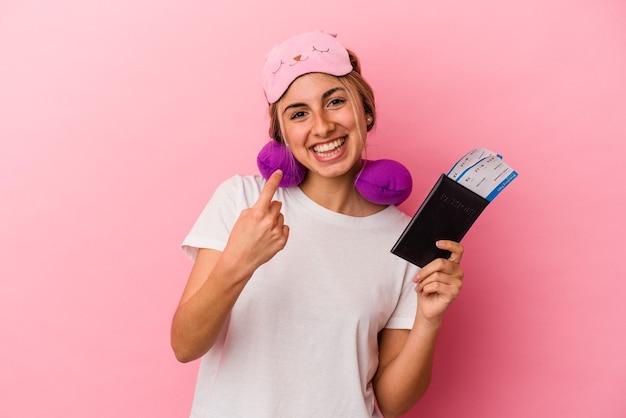 여권과 티켓을 들고 젊은 백인 금발의 여자는 초대 가까이 와서 당신 손가락으로 가리키는 분홍색 배경에 고립 된 여행.