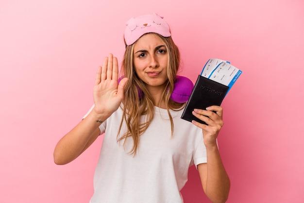 여권과 티켓을 들고 젊은 백인 금발의여자가 당신을 방지하는 정지 신호를 보여주는 뻗은 손으로 서 분홍색 배경에 고립 된 여행.