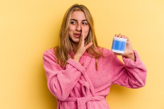 Молодая кавказская блондинка держит ватные палочки, изолированные на желтом фоне, говорит секретные горячие новости о торможении и смотрит в сторону