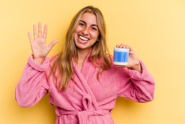 黄色の背景に分離された綿棒を持っている若い白人のブロンドの女性は、指で5番を示して陽気に笑っています。