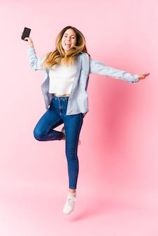 電話を保持し、ピンクの壁にジャンプする若い白人金髪女性
