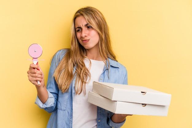 ピザと黄色の背景で隔離のカッターを保持している若い白人金髪女性