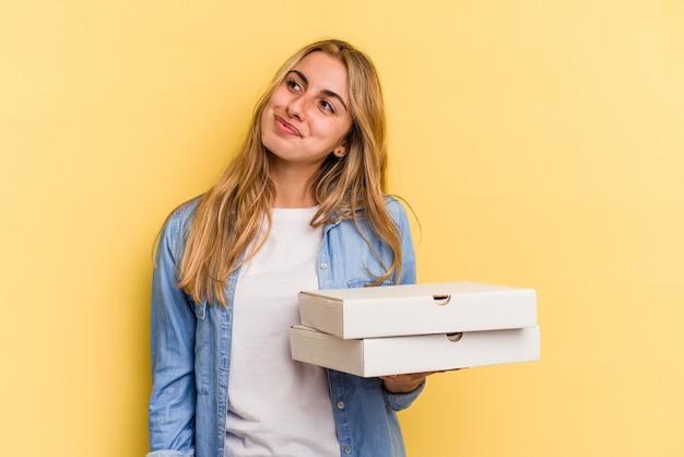目標と目的を達成することを夢見て黄色の背景に分離されたピザを保持している若い白人金髪女性
