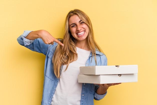 誇りと自信を持って、シャツのコピースペースを手で指している黄色の背景の人に分離されたピザを保持している若い白人のブロンドの女性