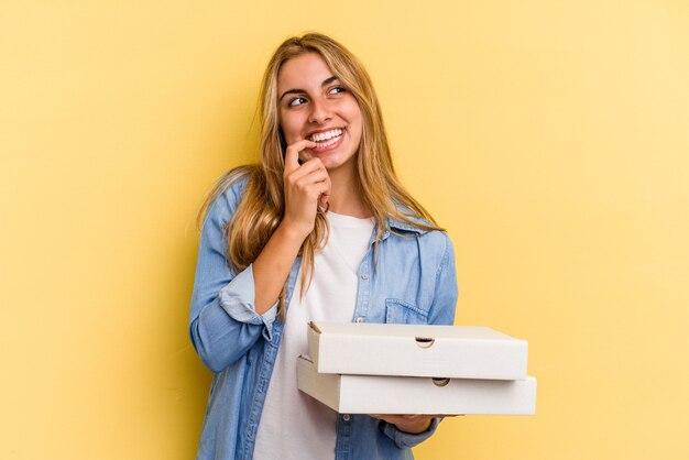노란색 배경에 격리된 피자를 들고 있는 백인 금발 여성은 복사 공간을 바라보는 무언가에 대해 편안하게 생각했습니다.
