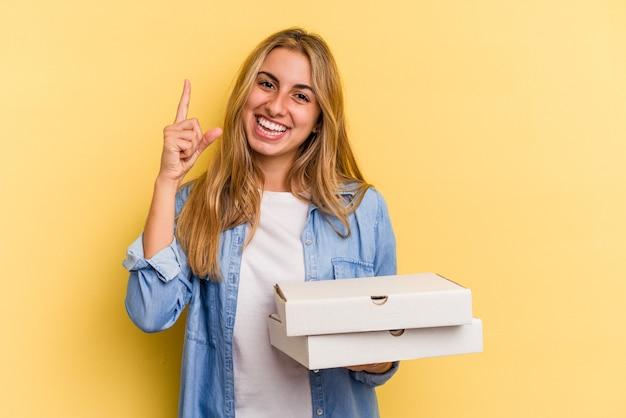 指でナンバーワンを示す黄色の背景に分離されたピザを保持している若い白人のブロンドの女性。