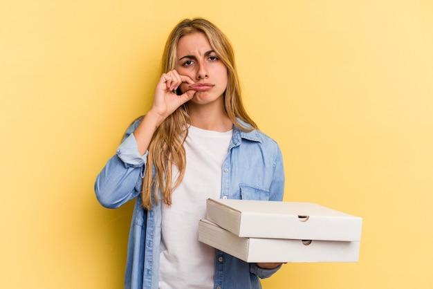 노란색 배경에 격리된 피자를 들고 입술에 손가락을 대고 비밀을 유지하는 젊은 백인 금발 여성.
