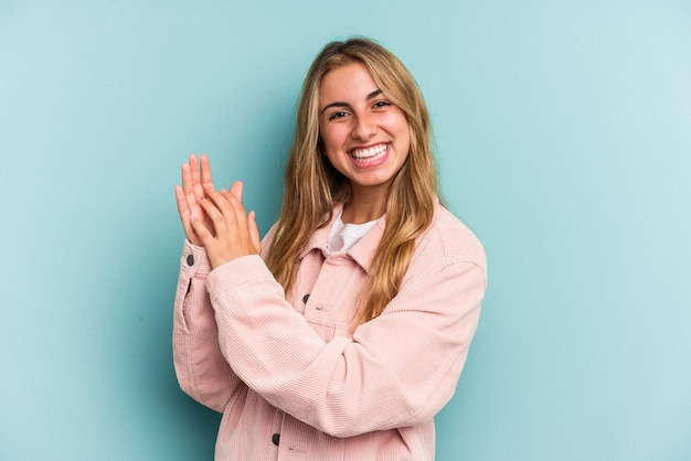 Young caucasian blonde woman isolated on blue background  feeling energetic and comfortable, rubbing hands confident.