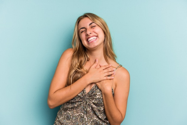 Young caucasian blonde woman isolated on blue background  laughing keeping hands on heart, concept of happiness.