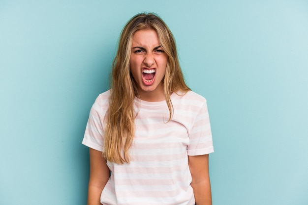 Young caucasian blonde woman isolated on blue background  shouting very angry, rage concept, frustrated.