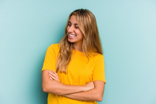 Young caucasian blonde woman isolated on blue background  smiling confident with crossed arms.