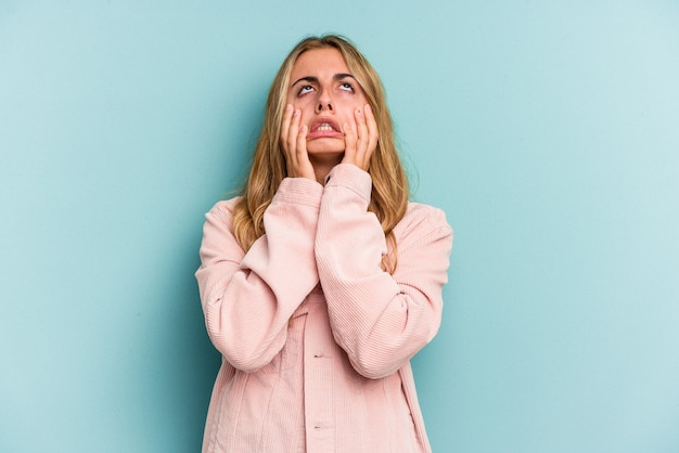 Young caucasian blonde woman isolated on blue background  whining and crying disconsolately.