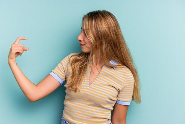 誘うようにあなたに指を指している青い背景に分離された若い白人のブロンドの女性が近づいています。